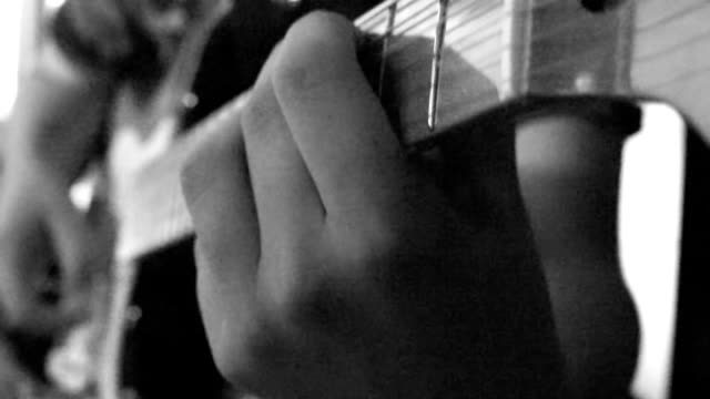 Boy playing guitar close up video