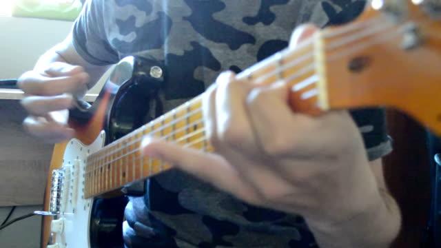 Boy playing guitar close up video