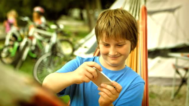 ハンドヘルドビデオゲームで遊ぶ少年 - 男の子点の映像素材/bロール