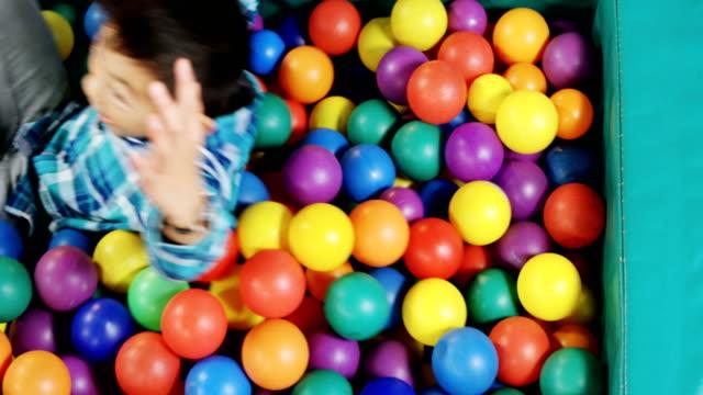 vídeos de stock e filmes b-roll de boy playing in ball pool 4k - brinquedos na piscina