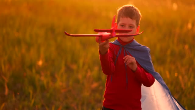 vídeos de stock e filmes b-roll de boy playing in the field with a plane in his hands at sunset - baby super hero