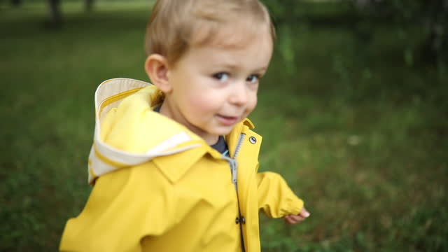 Boy playing in the rain, wearing boots and raincoat