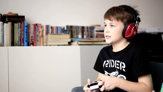 vídeos de stock e filmes b-roll de boy playing on games console - tv e familia e ecrã