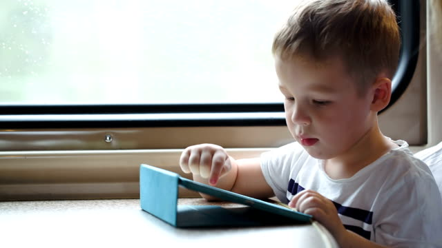 Boy playing on pad in the train trying to win video