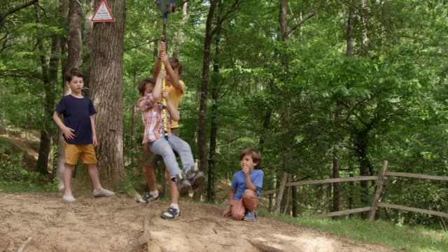 boy playing on rope and friends standing in forest - предподростковый возраст стоковые видео и кадры b-roll