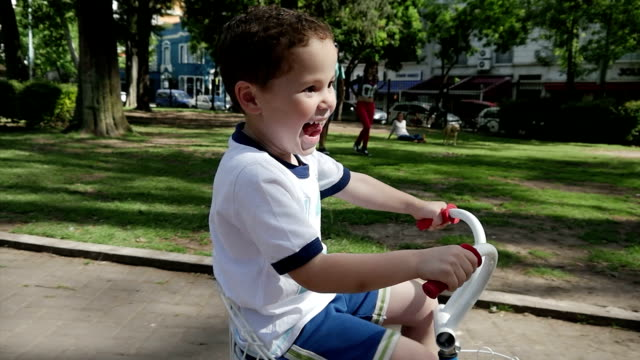 Boy playing & riding a tricycle slow motion - Happy video