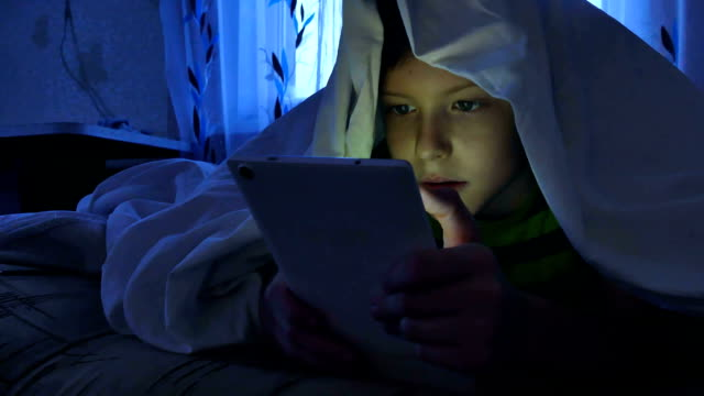 boy playing tablet night under a blanket video