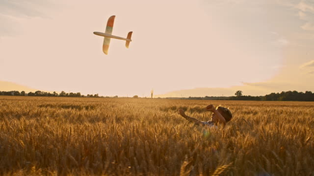 SLO MO Boy playing with airplane toy in the field