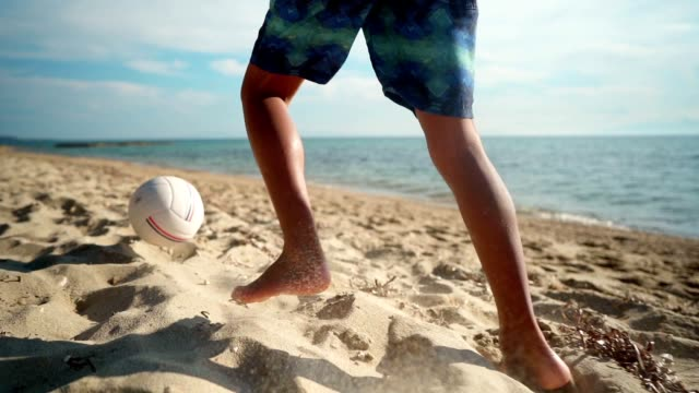 Boy playing with ball on the beach