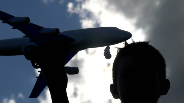 boy playing with toy airplane against beautiful sky video