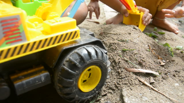 boy playing with toy backhoe and sand on ground,