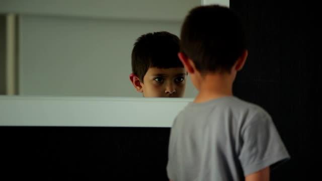 ragazzo gioca nella parte anteriore di uno specchio - brent video stock e b–roll