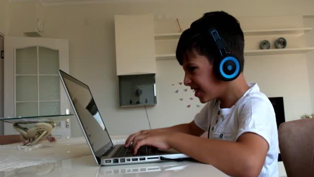 少年は再生ビデオゲーム ゲームのコンピューターのヘッドフォンを装着したまま - ゲーム ヘッドフォン点の映像素材/bロール