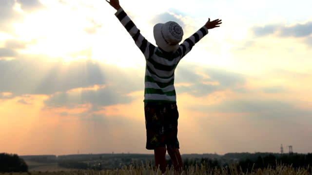 boy prays to God, the boy raises his arms up and looking at the sky in a field