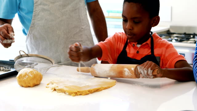Boy preparing cookie dough with his father and grandfather video