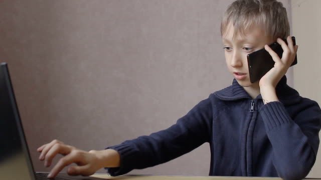 boy prints on a laptop and talking on the phone video