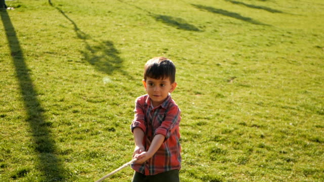 Boy pulling a rope and playing tug of war at the park