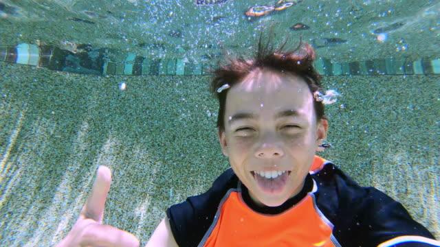 vídeos y material grabado en eventos de stock de niño tirando rostro bajo el agua - backyard pool