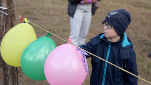 A boy punctures an inflatable balloon and it bursts video