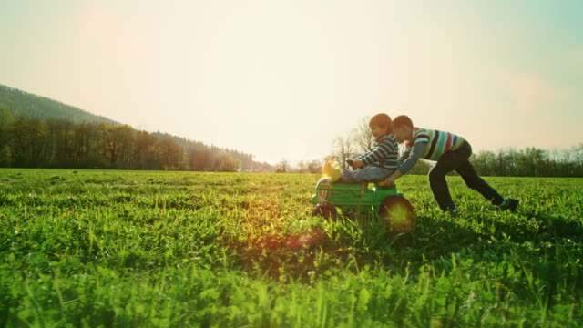 SLO MO Boy pushing his little brother sitting on a toy tractor across a meadow
