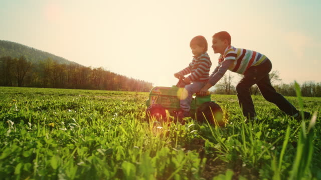 SLO MO TS Boy pushing his younger brother on a toy tractor in a sunny meadow