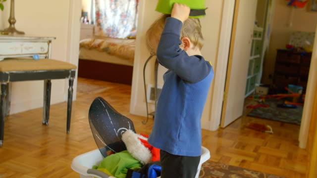 Boy puts felt bucket on his head video