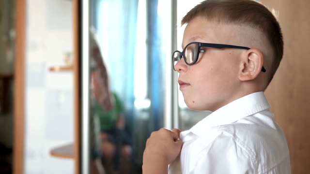 Boy puts on a white shirt, is going to school - vídeo