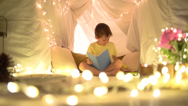 Boy reading a book past his bedtime