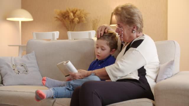 boy reading a book with grandmom - gente serena video stock e b–roll