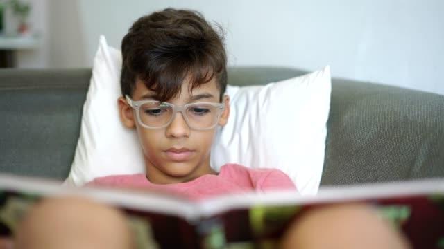 Boy reading book on sofa