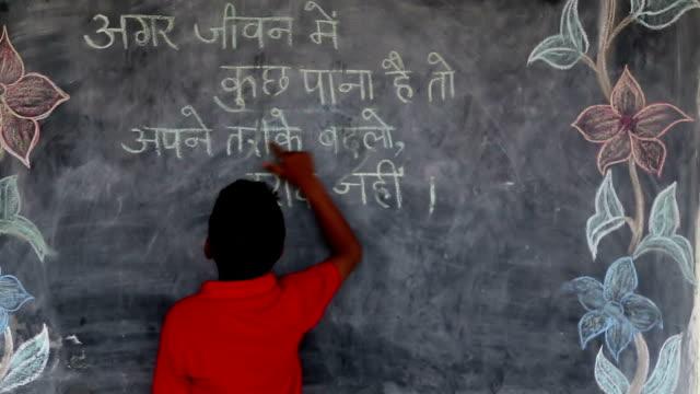 Boy reading text from blackboard