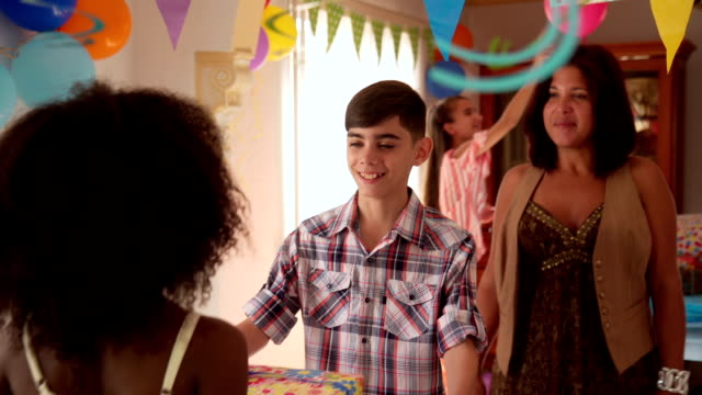 Boy Receiving Present From Girl During Birthday Party At Home video