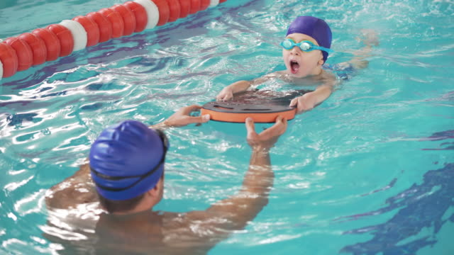 A boy receiving swimming lessons A boy receiving swimming lessons swimming stock videos & royalty-free footage