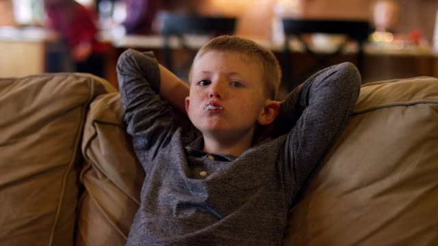Boy relaxing on the couch and chewing bubble gum, slow motion video