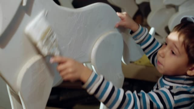 Boy repairing wolf figurine by painting it in white video
