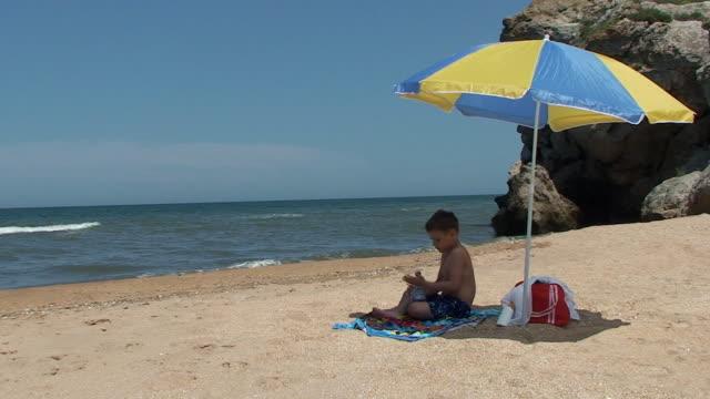 Boy resting on the beach video