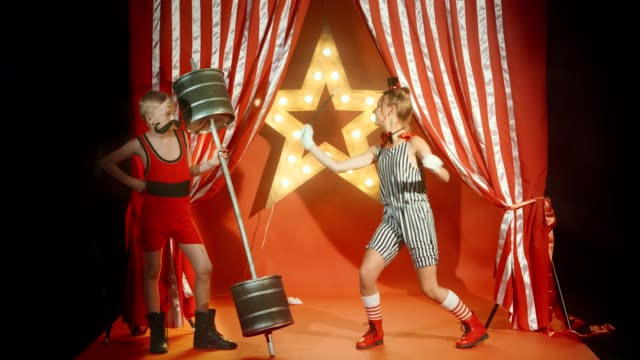 Boy retro strongman and cheerful girl magician shows funny circus performance