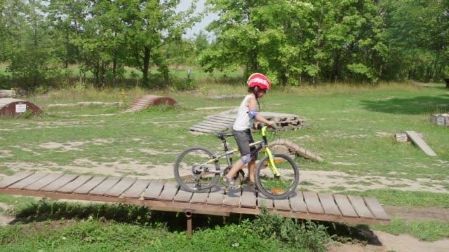 junge fährt mountainbike in einem extremen bike-fahrpark - fahrradfahren lernen close helmet stock-videos und b-roll-filmmaterial