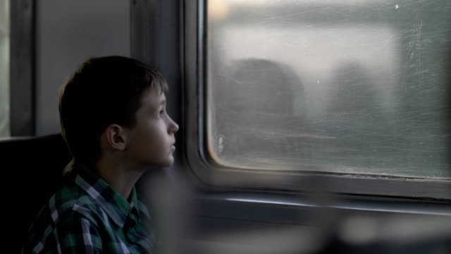 boy rides on a train in the evening looks out the window video