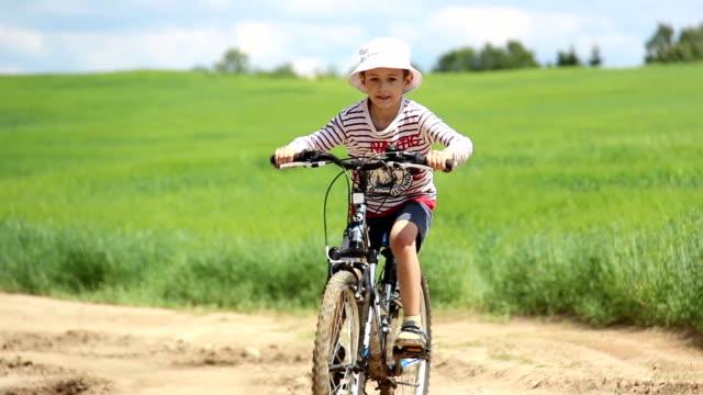 boy riding a bike on rural road in field video