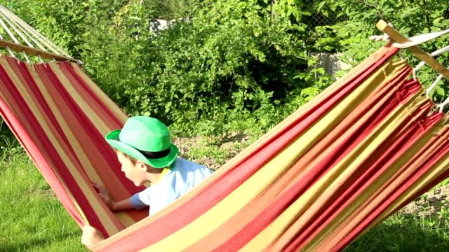 Boy riding a hammock having fun, spending time outdoors video