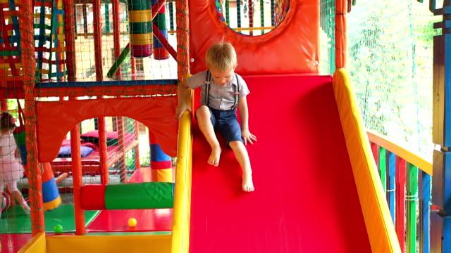 Boy riding from children's slides in game center. video