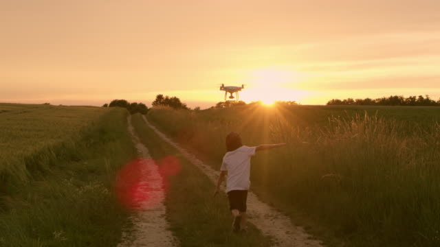 SLO MO Boy running after a drone Slow motion shot of a little boy with an aviator's cap running after a drone flying along dirt road among wheat fields at sunset. only boys stock videos & royalty-free footage