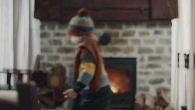 vídeos de stock e filmes b-roll de boy running in front of the fireplace - living room background