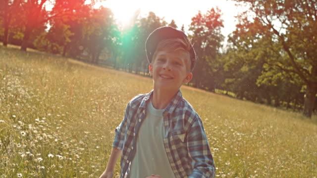 slo mo ts мальчик бег в высокой траве в лето - предподростковый возраст стоковые видео и кадры b-roll