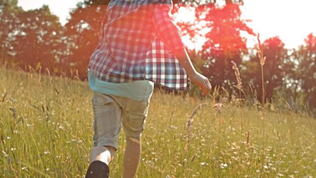SLO MO TS Boy running through high grass in sunshine video