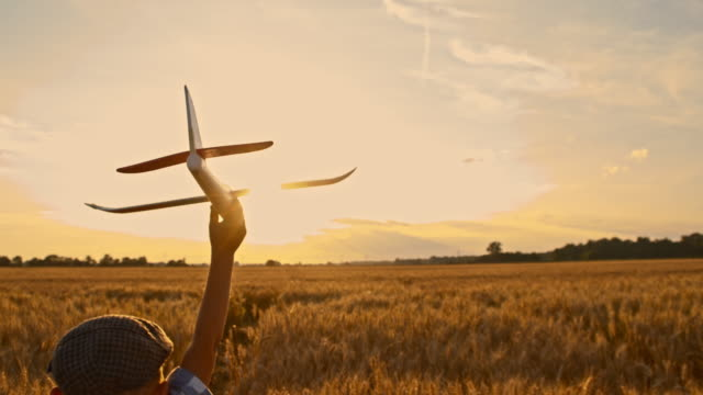 SLO MO Boy running with airplane toy through wheat field video