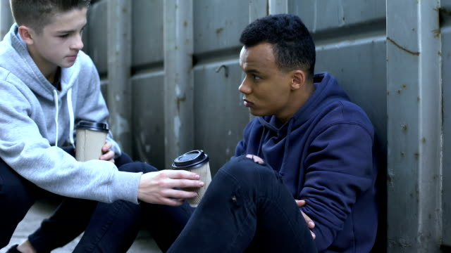 Boy sharing warm coffee with frozen homeless teenager, charity volunteer
