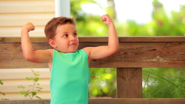 junge zeigt seine muskeln - muskulös stock-videos und b-roll-filmmaterial