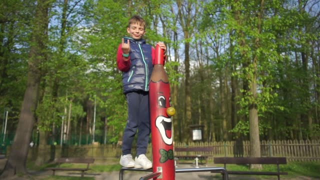 boy shows like gesture standing on a wooden totem